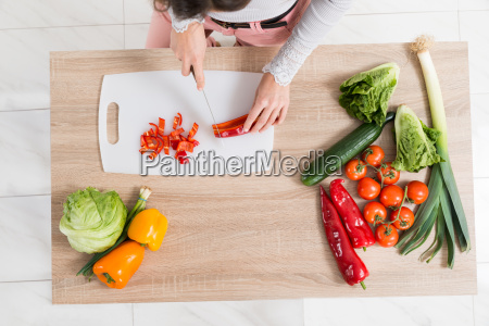 woman chopping vegetable on countertop