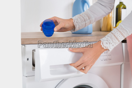 female hands pouring detergent in the