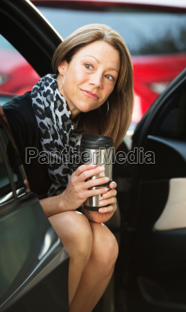 cute worker with coffee in car