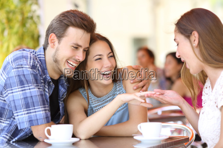 couple showing his engagement ring to