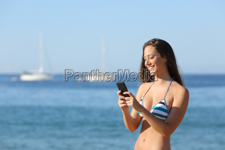 sunbather girl using a smart phone