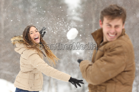 couple playing with snow and girlfriend