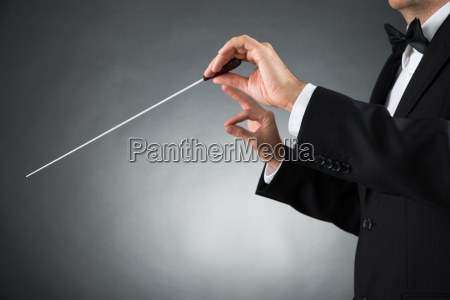 orchestra conductor holding baton