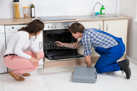 woman looking at worker repairing oven