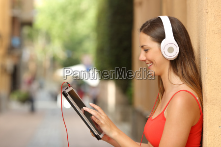 girl browsing a tablet and listening