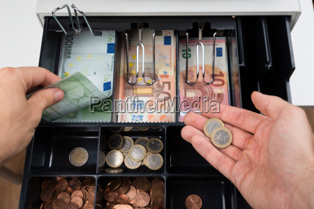 person hands with money over cash