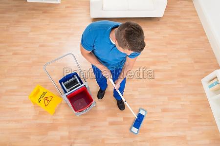 worker mopping wooden floor