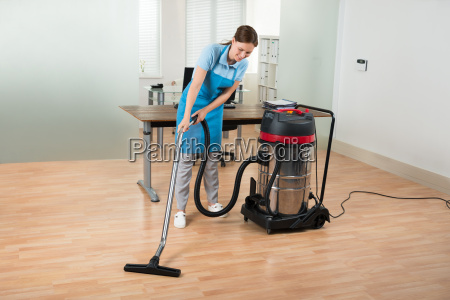 worker cleaning floor with vacuum cleaner