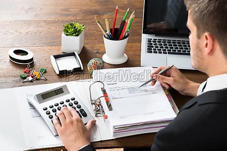 businessman calculating receipt at desk