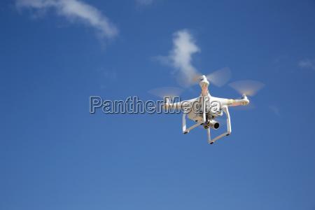 drone flies against blue sky on