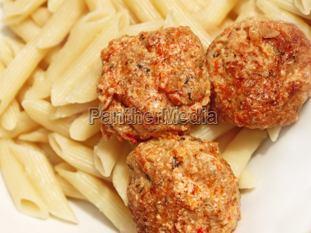 three meatballs with sauce over pasta