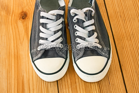 pair of sneakers on the wooden