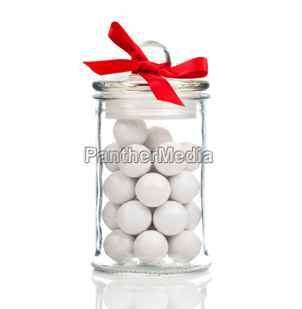 white candies gumballs in glass on