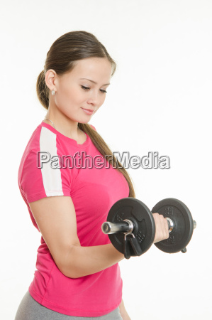 girl athlete is looking at dumbbell