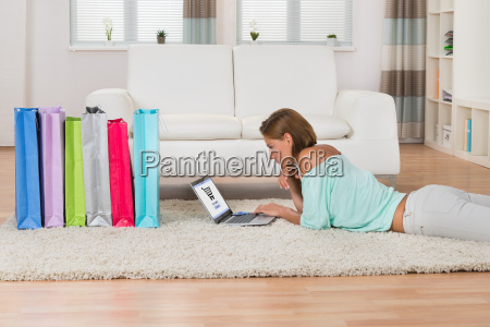 woman with laptop lying on carpet