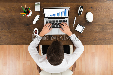 businessperson analyzing graph on laptop