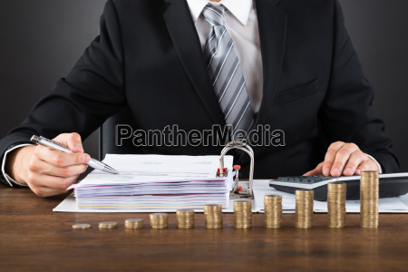 businessman calculating invoice with coins at