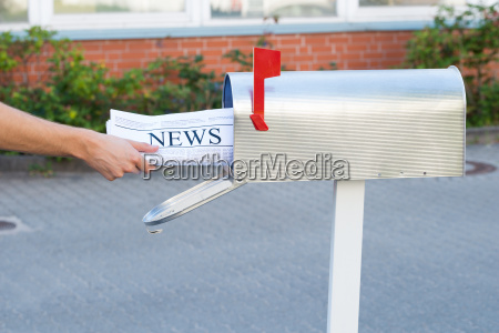 person hands opening mailbox to remove