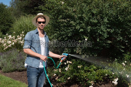 young handsome man is watering the
