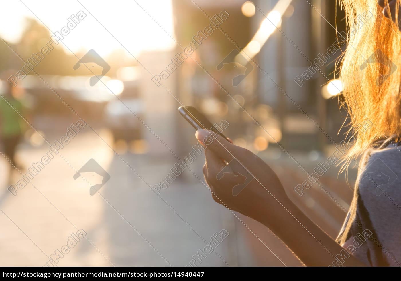 closeup, women, using, smartphone, at, sunset - 14940447