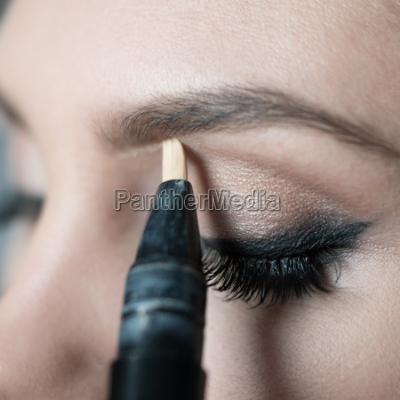 close up of woman applying make