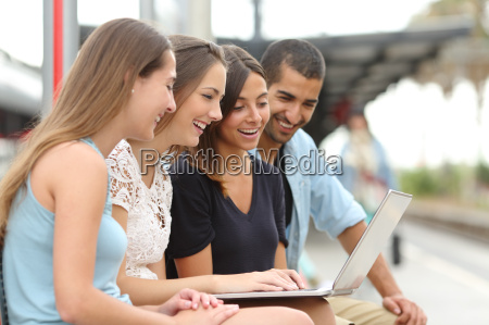 four friends using a laptop in