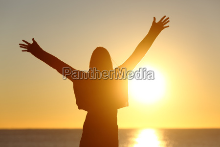 free woman raising arms watching sun