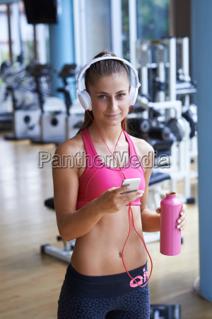 woman with headphones in fitness gym