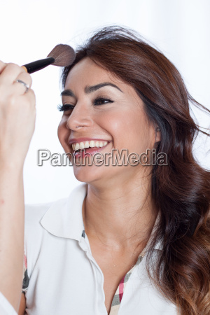 woman smiling with a makeup brush
