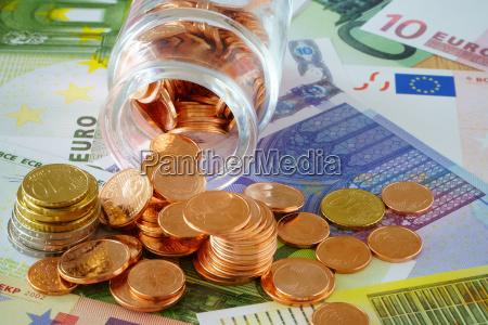 coins in glasfaeschchen and euro banknotes