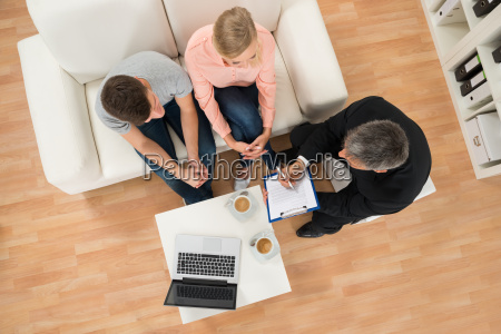 consultant showing document to couple