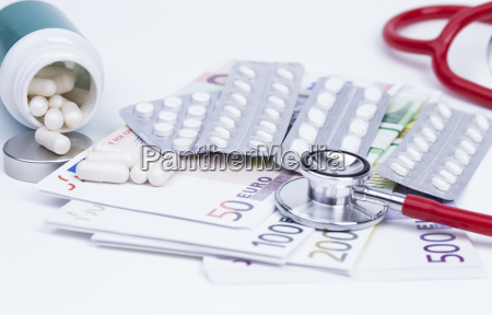 tablets with money and stethoscope