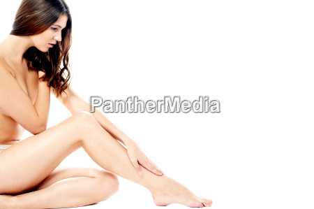 beautiful woman applying moisturiser