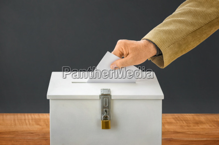 man throws ballot paper in election