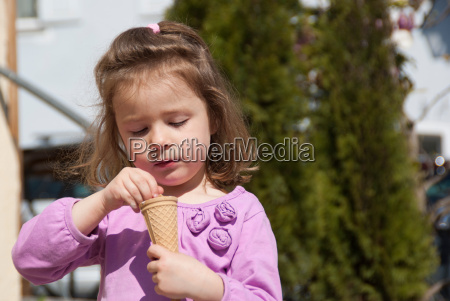 a little girl eats an ice
