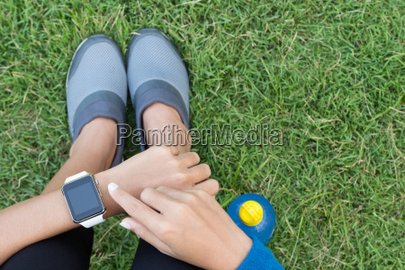 athletic woman using smartwatch on top