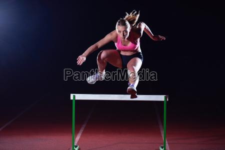 woman athlete jumping over a hurdles