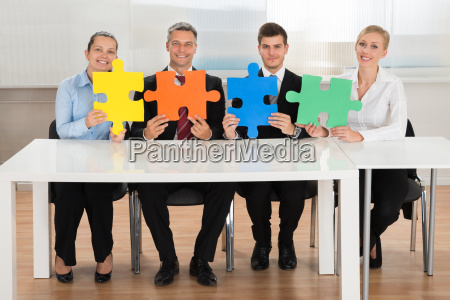 businesspeople holding multi colored puzzles