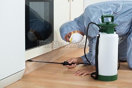 exterminator spraying pesticide on wooden cabinet