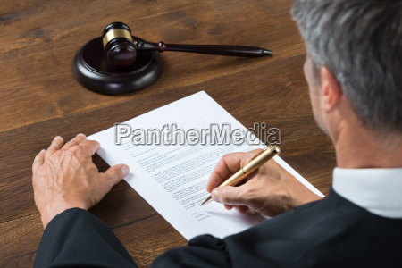 judge writing on paper in courtroom