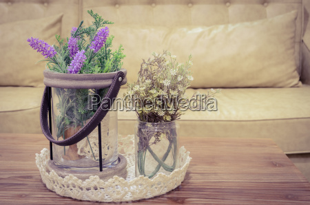 artificial flowers on wooden table with