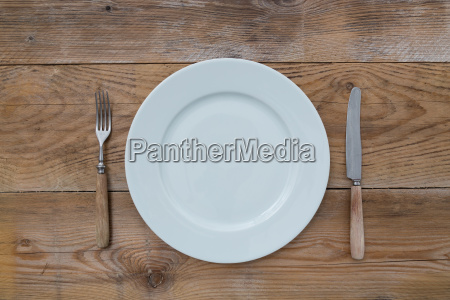 white plate and cutlery on wood