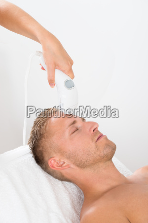 young man receiving laser hair removal