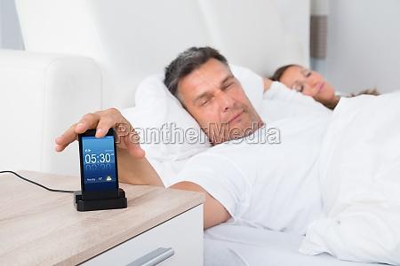 man on bed snoozing alarm clock