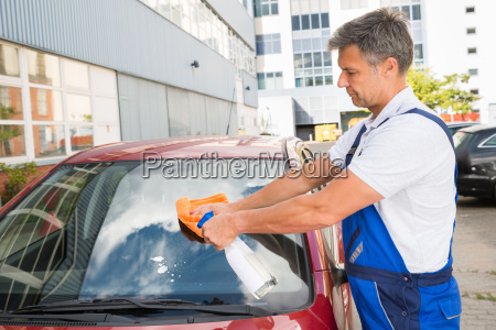 worker cleaning car windshield
