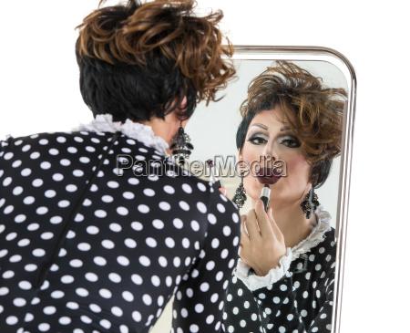 drag queen use lipstick near mirror