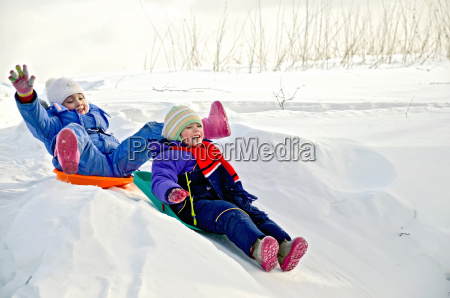 two little girls on sled through