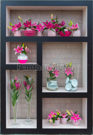 lilies in vases stand on shelves