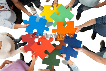 creative business people holding colorful puzzle