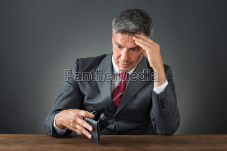 shocked businessman with empty wallet